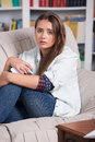 Young girl is crying sitting on the couch teenage with phone in hand while Stock Photo