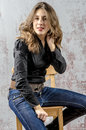 Young girl with curly hair in a black shirt, jeans and high boots cowboy western style Royalty Free Stock Photo