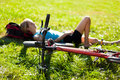 Young girl cyclist enjoying relaxation lying in the fresh green Stock Images