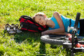 Young girl cyclist enjoying sleeps relax lying in the fresh gras Stock Photography