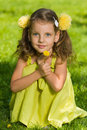 Young girl with dandelion a smiling is sitting on the green grass Stock Photo
