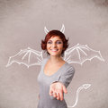 Young girl with devil horns and wings drawing nasty Stock Photos
