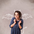 Young girl with devil horns and wings drawing nasty Stock Image