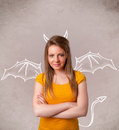 Young girl with devil horns and wings drawing nasty Royalty Free Stock Image