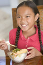 Young girl in dining room eating Chinese food Stock Image