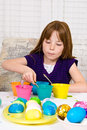 Young girl dipping hard boiled egg blue dye process coloring easter eggs egg completely dye Stock Image