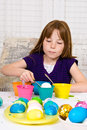 Young girl dipping hard boiled egg blue dye process coloring easter eggs egg now partially dipped cup dye Royalty Free Stock Photos