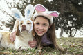Young girl and dog with bunny ears on smiling holding her Stock Image