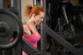 Young girl doing squats with barbell red haired on smith machine Stock Images
