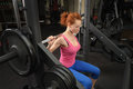 Young girl doing squats with barbell red haired on smith machine Royalty Free Stock Photos