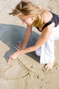 Young girl drawing a heart shape on sand Royalty Free Stock Images