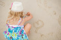 Young girl drawing heart shapes in sand Royalty Free Stock Photos