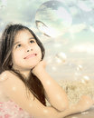 Young girl dreaming gazing dreamily at her reflection in a large bubble Stock Images