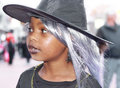 A young girl dressed as a witch making her way around town at a halloween festival Stock Photos