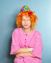 Young girl dressed like a cloun portrait of nyoung in funny striped suit red wig and colorful hat Royalty Free Stock Photo