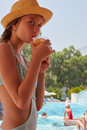 Young girl with drink at poolside Royalty Free Stock Photo