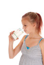 Young girl drinking a glass of milk in gray dress holding and it isolated for white background Stock Photos