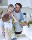 Young girl eating carrot with parents Stock Photography