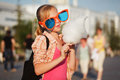 Teen girl in sunglasses eating cotton candy on city street Royalty Free Stock Photo
