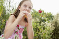 Young girl eating cupcake against plants sitting in meadow and Stock Images