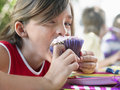 Young girl eating cupcake at birthday party portrait of little the outdoor Royalty Free Stock Photo