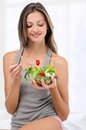 Young girl eating fresh salad Royalty Free Stock Images