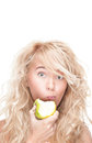 Young girl eating green apple on white background. Royalty Free Stock Photo