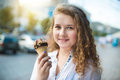 Young girl eating ice cream in the city street Stock Image