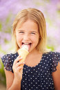 Young girl eating ice cream outdoors looking to camera Royalty Free Stock Image