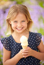 Young girl eating ice cream outdoors smiling to camera Stock Photography