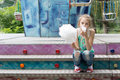 Young girl eating a stick of candy floss in the summer sunshine sitting on flight colorful steps at playground or fair Royalty Free Stock Images