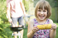 Young Girl Eating Sweetcorn At Family Barbeque Royalty Free Stock Photo