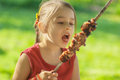 Young girl eats kebab little with pleasure shish Stock Photos