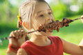Young girl eats kebab little with pleasure shish Royalty Free Stock Photo