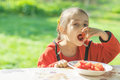 Young girl eats vegetables little sits at table in garden of parents and cut Royalty Free Stock Photography
