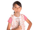 Young girl with egg beater ii asian malay in kitchen apron holding an over white Stock Photo
