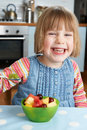 Young girl enjoying bowl of fresh fruit for pudding enjoys Royalty Free Stock Photos