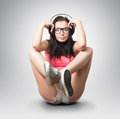 Young girl in an extravagant pose with headphones on background Royalty Free Stock Photo