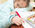 Young girl falling asleep doing homework Royalty Free Stock Photo