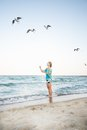 Young girl are feeding seagulls at beach Stock Images