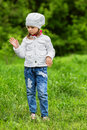 Young girl flapping mosquitoes away standing on a green lawn and Royalty Free Stock Photography