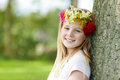 Young girl with floral wreath leaning on a tree Royalty Free Stock Photo