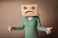 Young girl gesturing with brown cardboard box on her head with s standing and sad face Stock Images