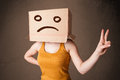 Young girl gesturing with brown cardboard box on her head with s standing and sad face Royalty Free Stock Images