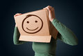 Young girl gesturing with a cardboard box on her head with smile standing and smiley face Stock Image