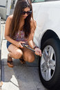 Young girl gets ready to add air to car tire Royalty Free Stock Photos