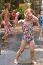 Young girl gets sprayed face water playing hot summer afternoon Royalty Free Stock Images
