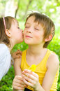 Young girl gives her brother a kiss on the cheek outdoors Stock Photo