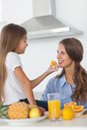 Young girl giving an orange segment to her mother in the kitchen Royalty Free Stock Image
