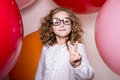 Young girl in glasses showing two fingers victory against the ba background of large colorful balloons Stock Photo